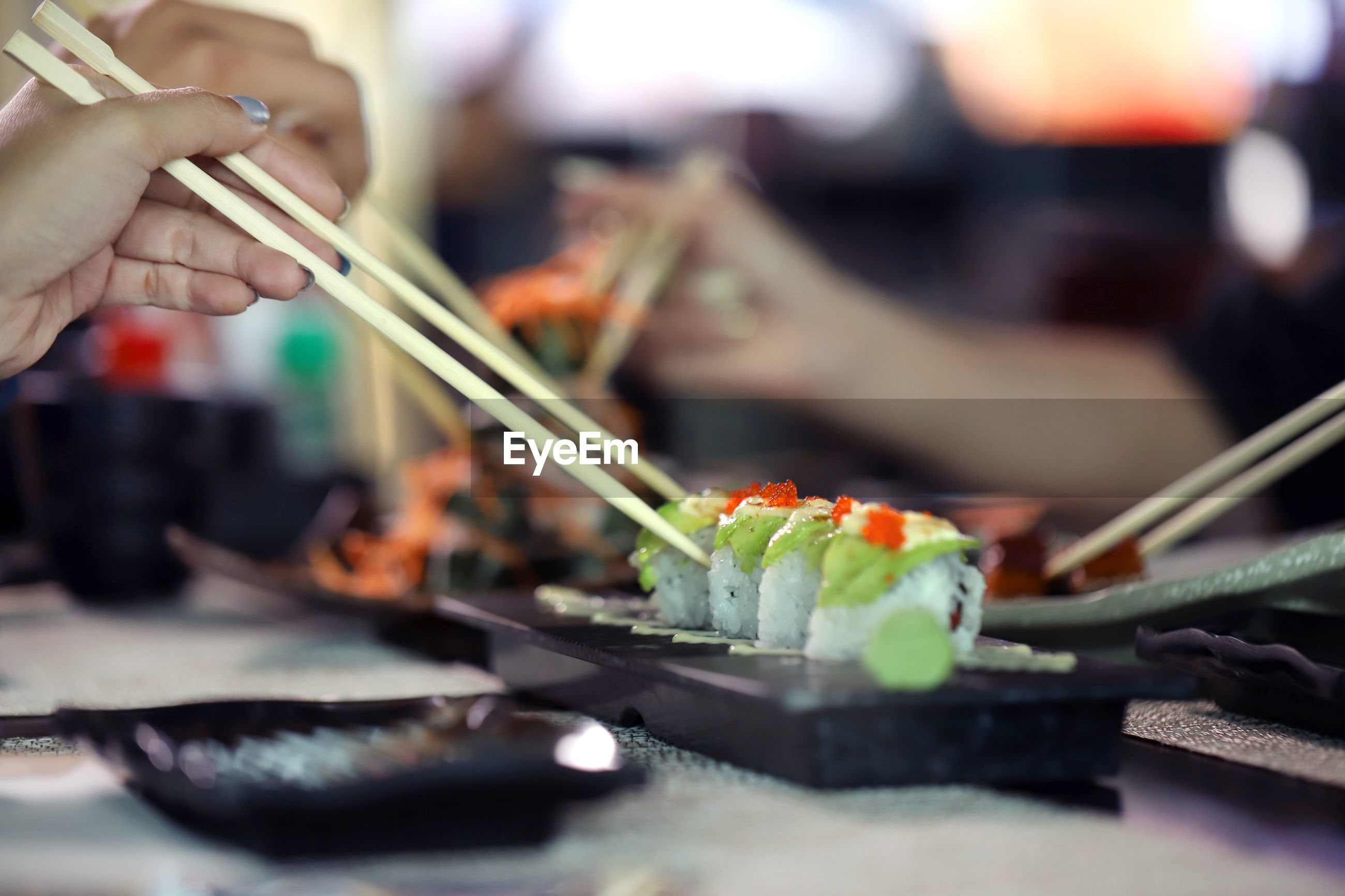 Close-up of woman hands holding sushi with chopsticks on table