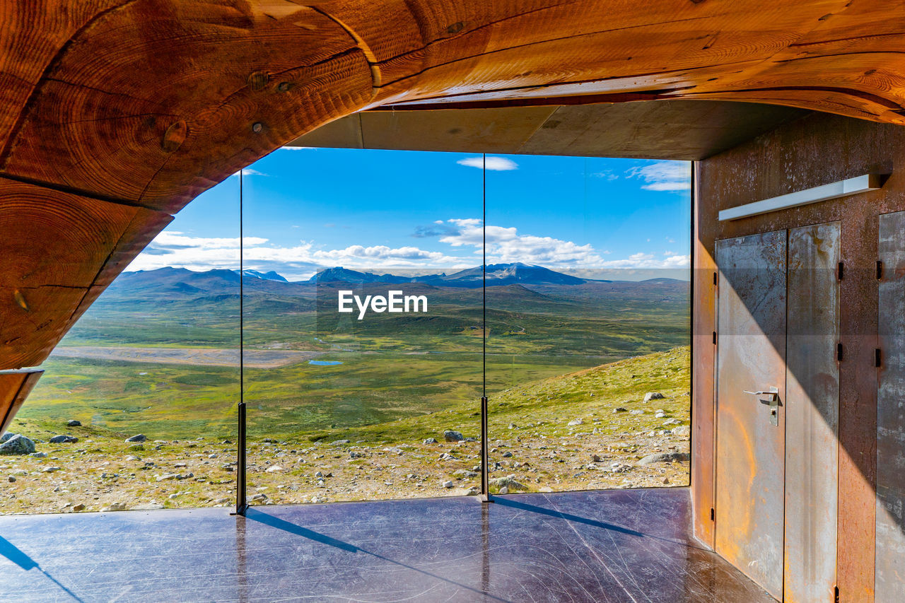 nature, mountain, no people, landscape, day, window, sky, architecture, indoors, land, beauty in nature, environment, scenics - nature, sunlight, wood - material, cloud - sky, mountain range, glass - material, transportation