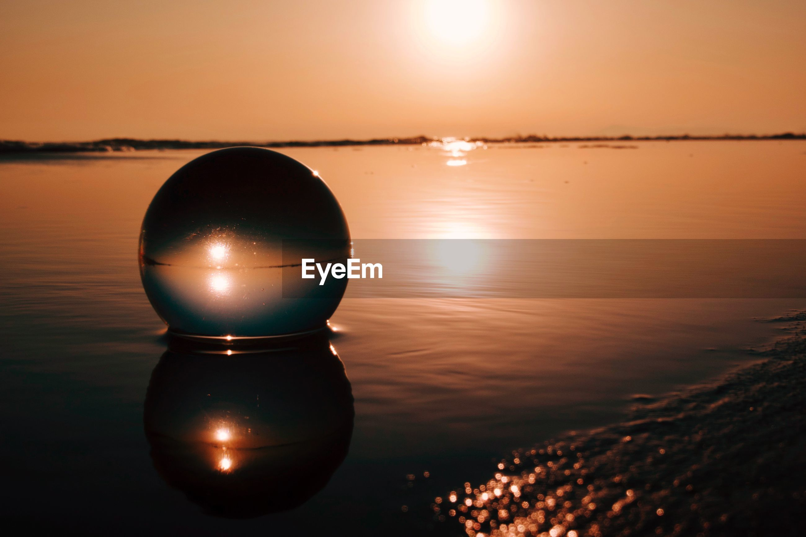 Scenic view of crystal ball in the sea against sky during sunset