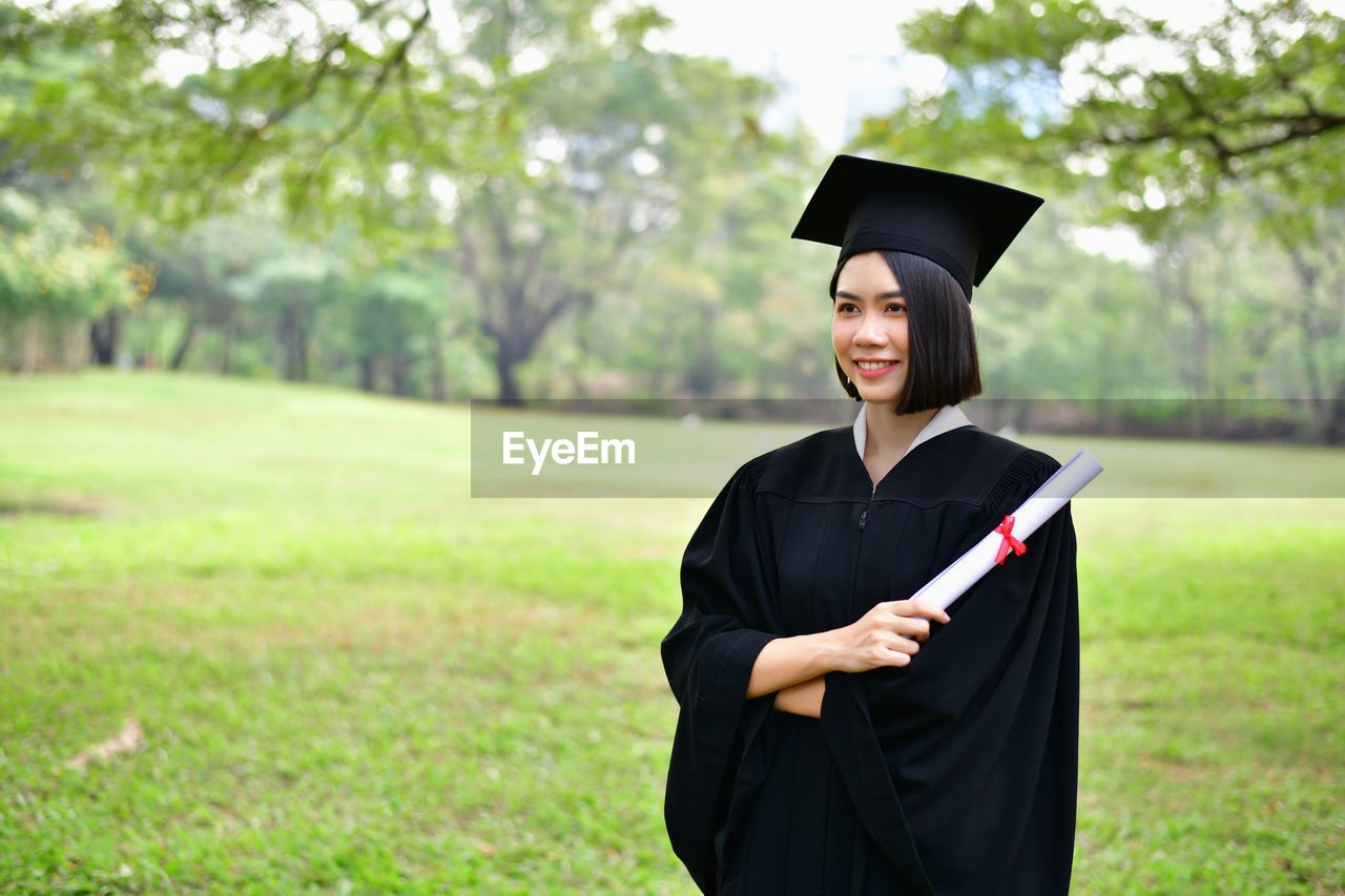 graduation gown, mortarboard, graduation, student, university student, university, education, young adult, achievement, focus on foreground, real people, smiling, standing, day, people, young women, happiness, success, portrait, school, outdoors