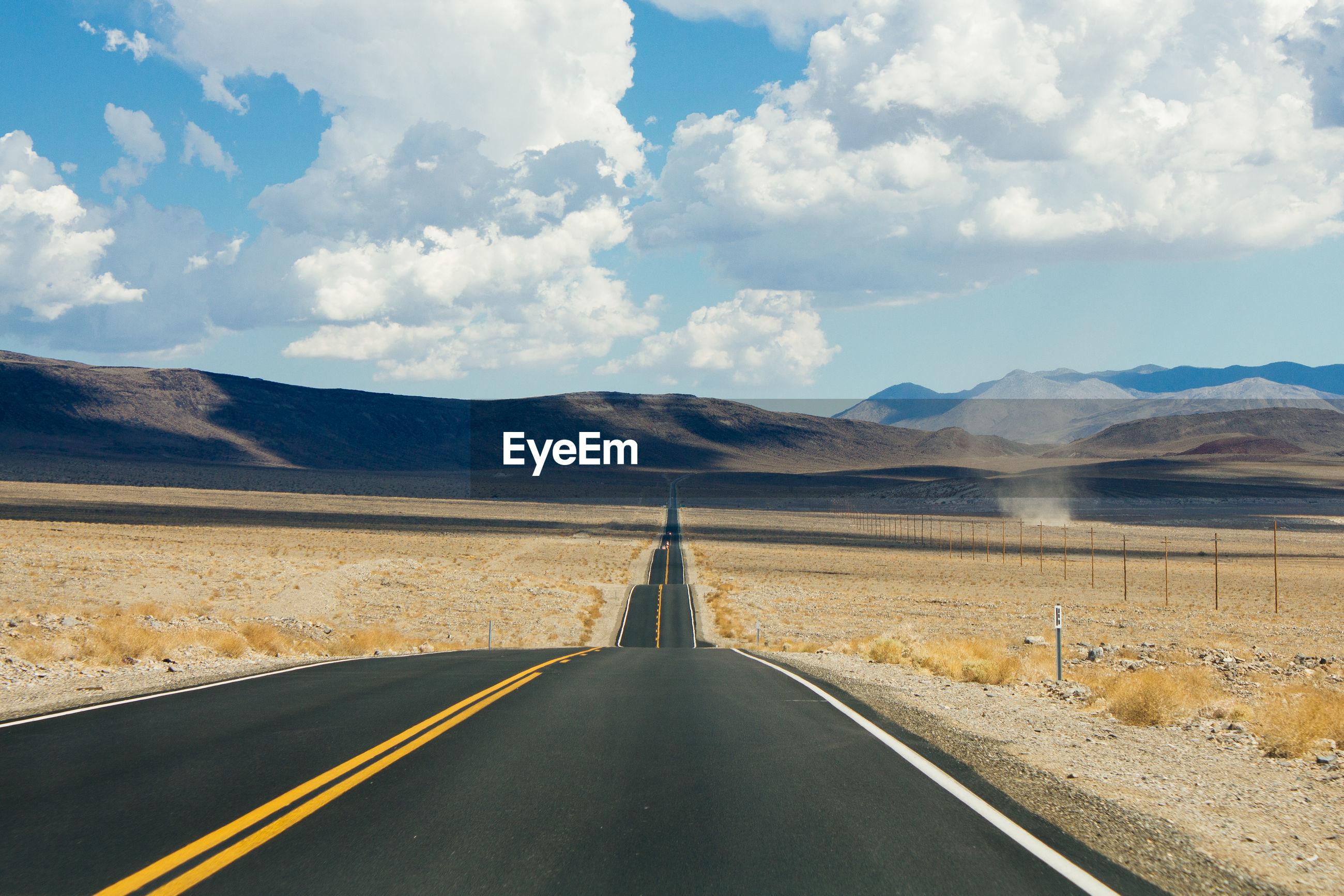 Empty desert road towards mountains against sky