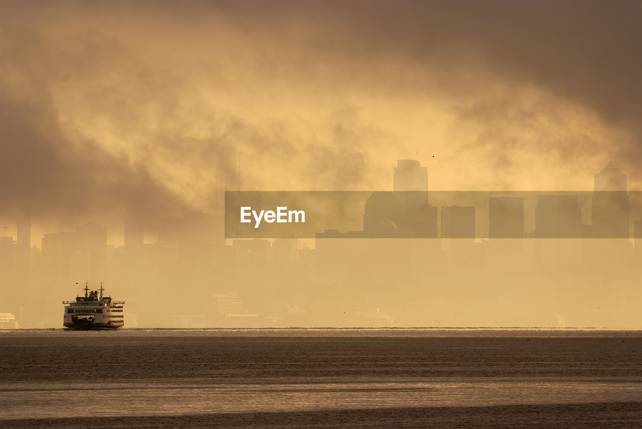 Ferry boat in sea against skyline during sunset