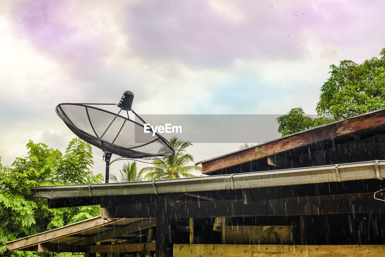 cloud - sky, sky, architecture, built structure, nature, connection, satellite, plant, no people, tree, low angle view, roof, day, satellite dish, building exterior, outdoors, bridge, communication, antenna - aerial, technology, global communications