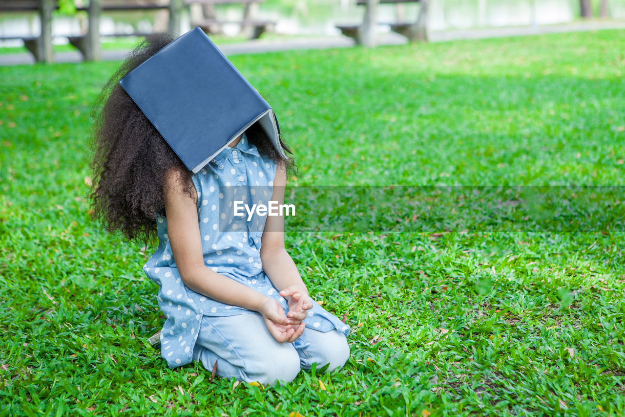 Bored girl covering face with book on grassy land in park