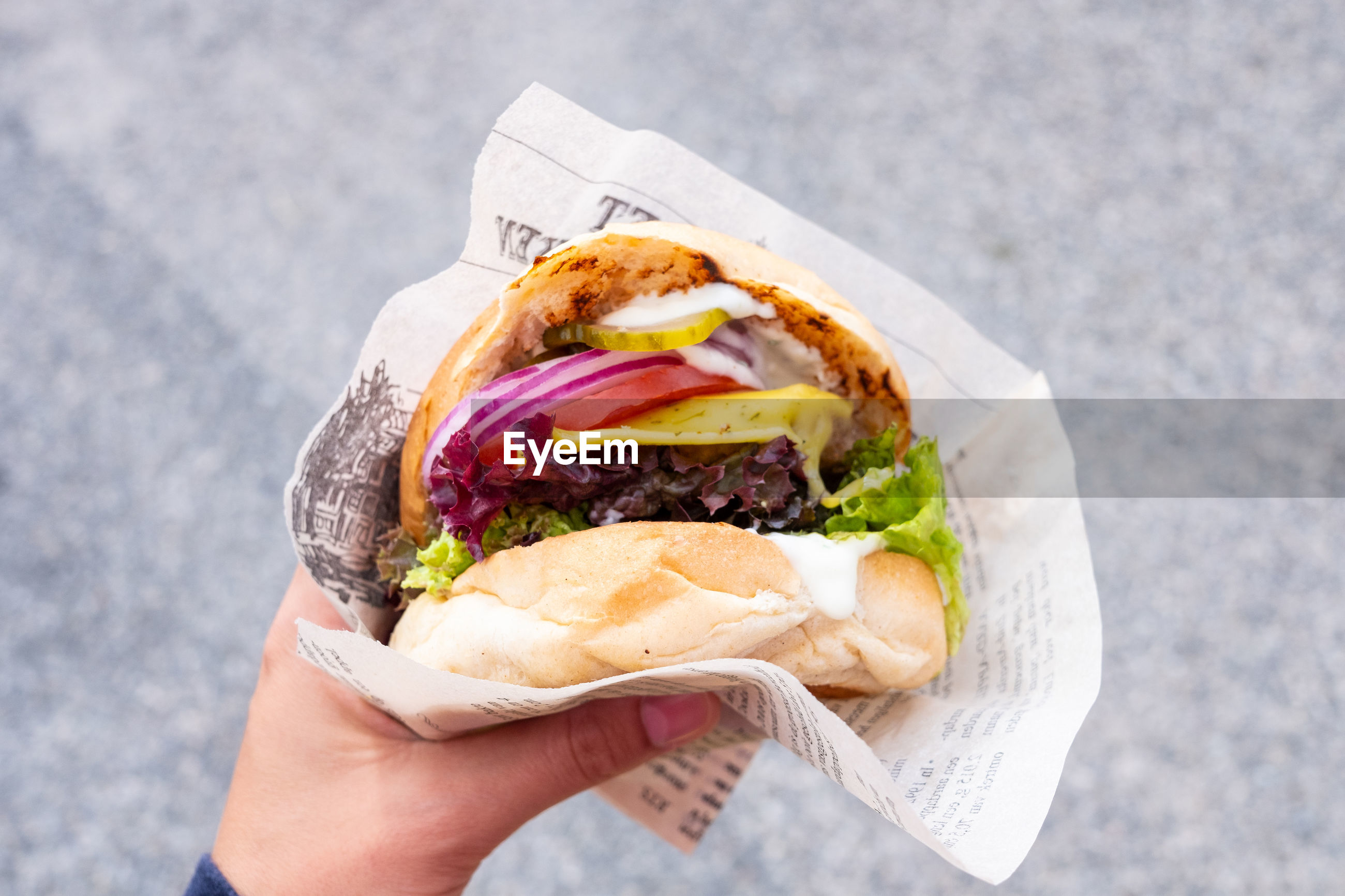Cropped hand of person holding burger