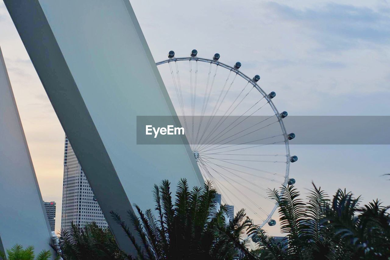 ferris wheel, low angle view, amusement park, sky, arts culture and entertainment, big wheel, day, outdoors, amusement park ride, tree, no people, architecture