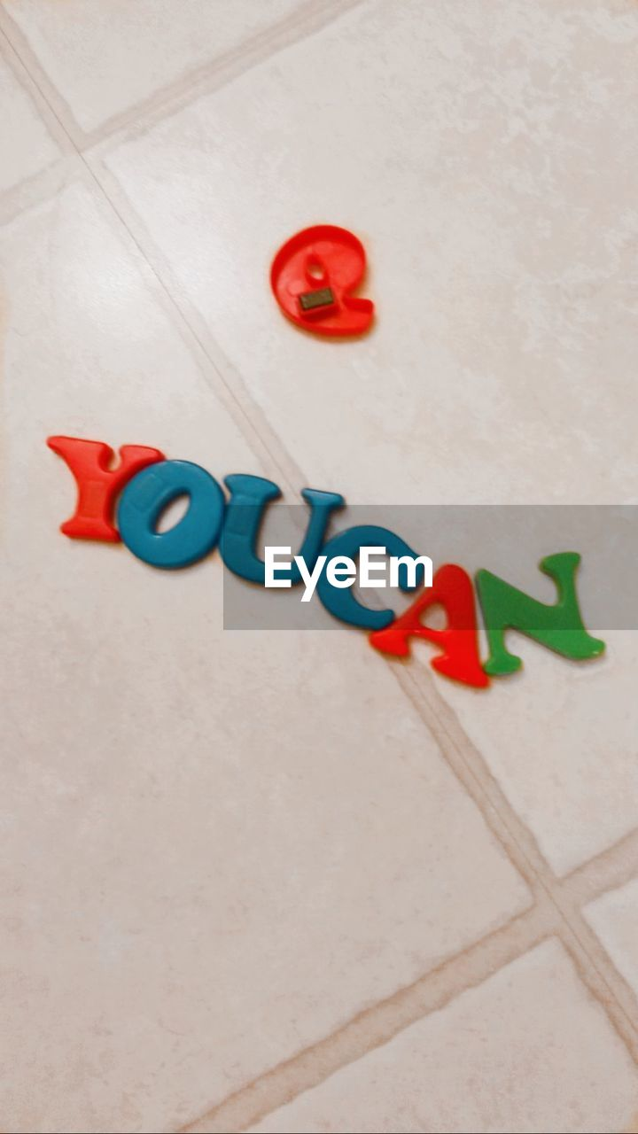 High angle view of multi colored letters on floor