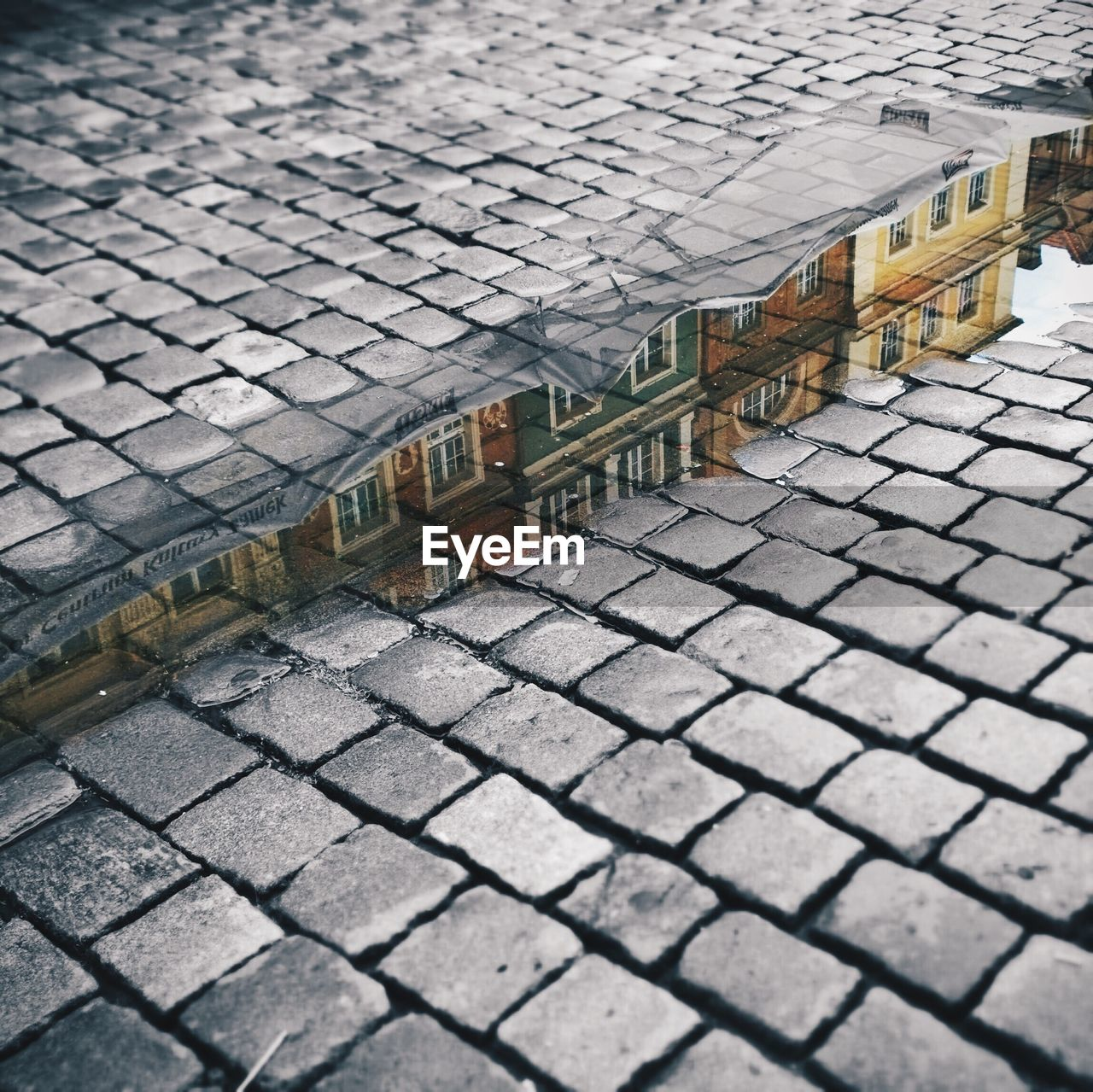 Reflection of buildings in puddle on cobbled street