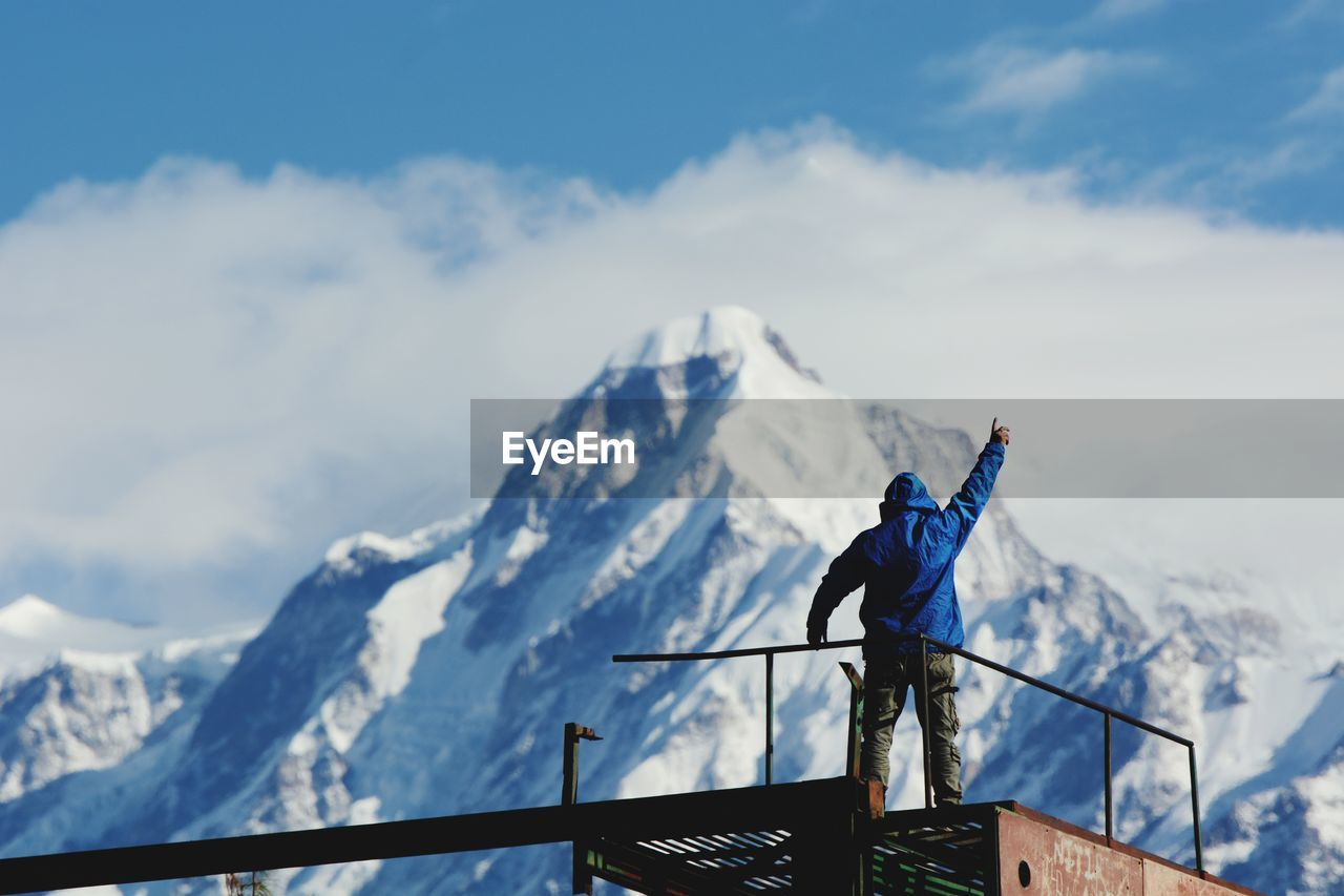 Man With Arms Raised Standing On Observation Point By Snowcapped Mountains