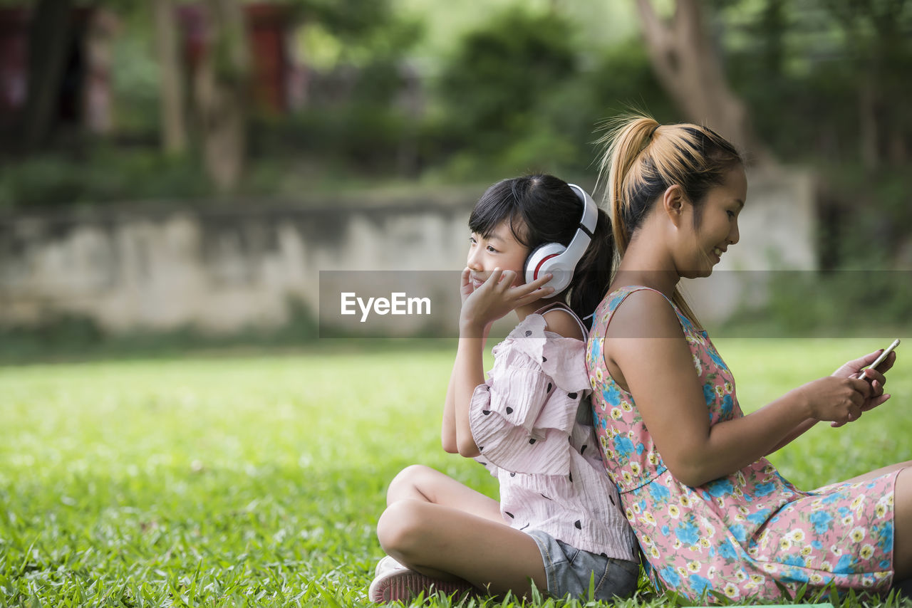 real people, women, sitting, leisure activity, focus on foreground, two people, casual clothing, three quarter length, young adult, lifestyles, young women, day, girls, mobile phone, communication, using phone, people, adult, females, hairstyle, outdoors