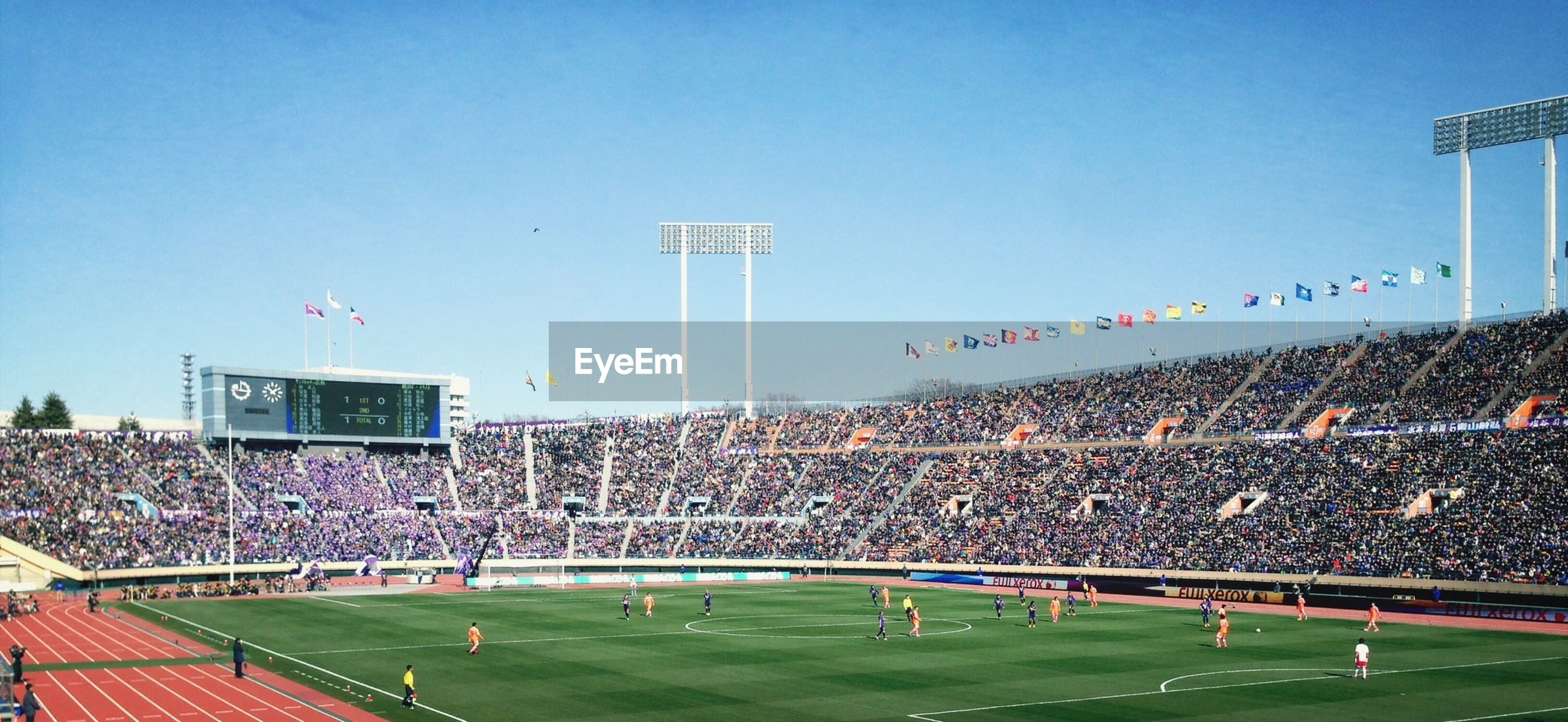 large group of people, clear sky, built structure, building exterior, architecture, blue, flying, leisure activity, person, lifestyles, grass, sport, crowd, tree, men, city, landscape, high angle view, sky