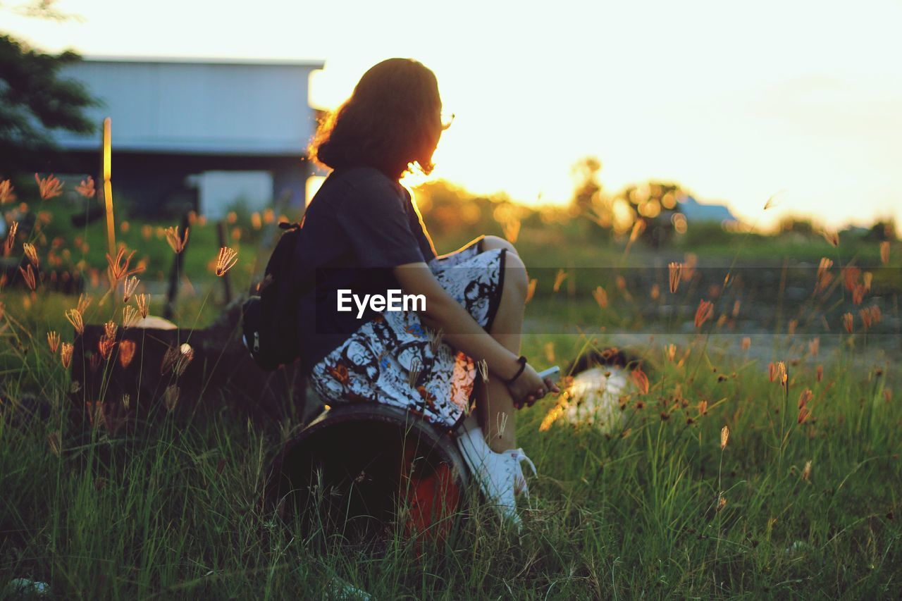 Side View Of Woman Sitting On Pipe At Grassy Field During Sunset