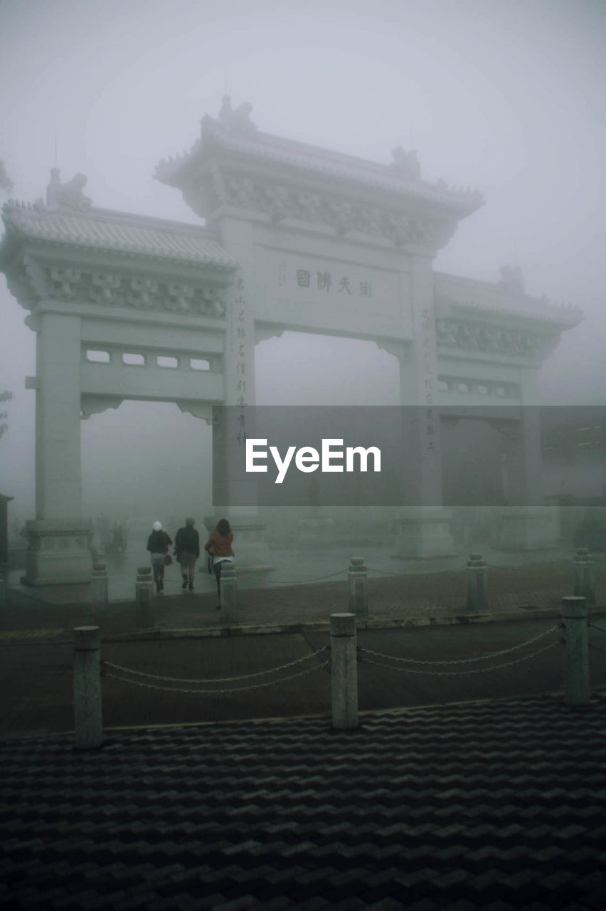 Rear view of people walking towards entrance of ngong ping