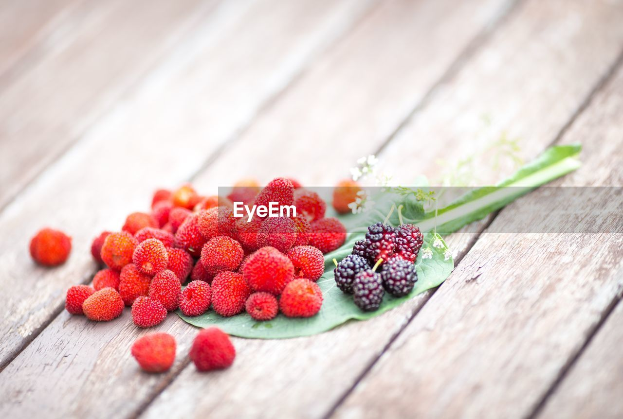 food and drink, wood - material, berry fruit, food, healthy eating, table, fruit, red, freshness, still life, close-up, wellbeing, raspberry, no people, strawberry, selective focus, indoors, high angle view, focus on foreground, temptation, lychee