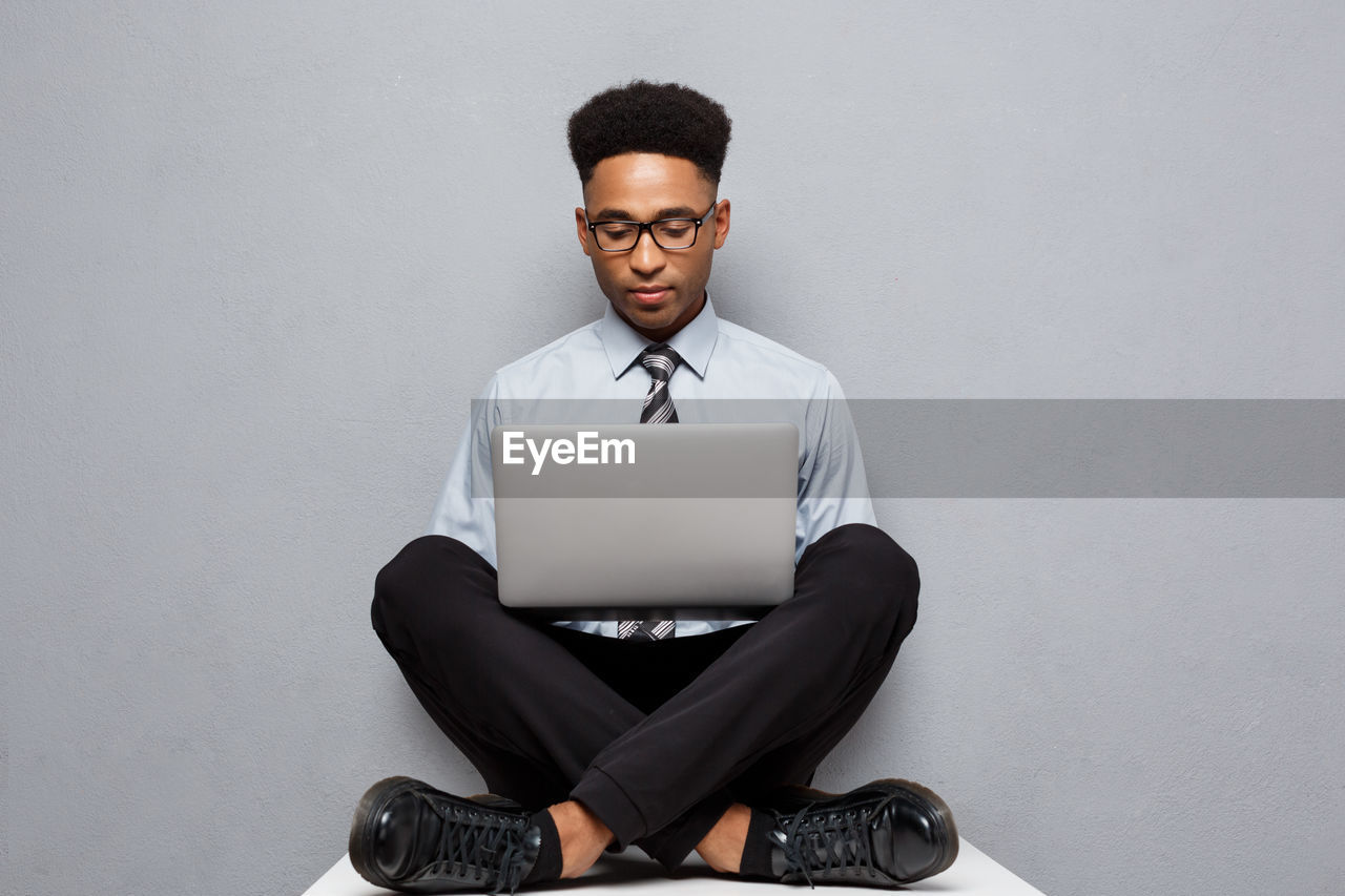 Businessman Using Laptop While Sitting On Table Against Gray Background