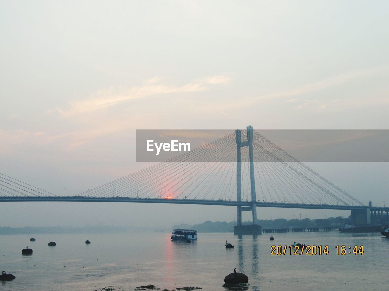 bridge - man made structure, suspension bridge, connection, transportation, engineering, sky, water, architecture, built structure, river, bridge, mode of transport, cloud - sky, no people, travel destinations, outdoors, fog, sunset, city, travel, nautical vessel, scenics, day, nature, beauty in nature
