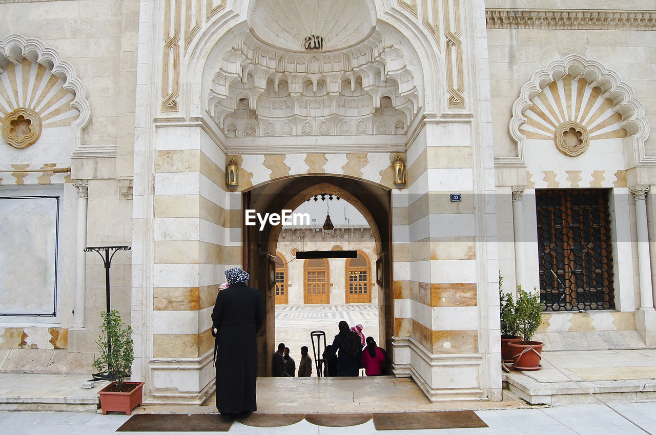 arch, architecture, built structure, building exterior, entrance, real people, building, women, history, day, the past, group of people, adult, men, door, lifestyles, people, place of worship, religion, full length, outdoors, architectural column