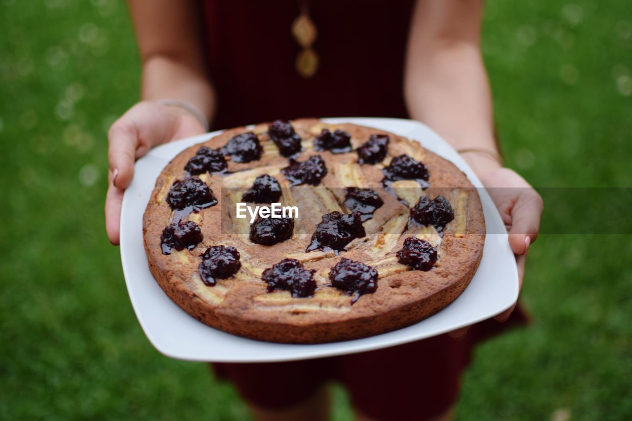 Midsection Of Woman Holding Tart On Plate