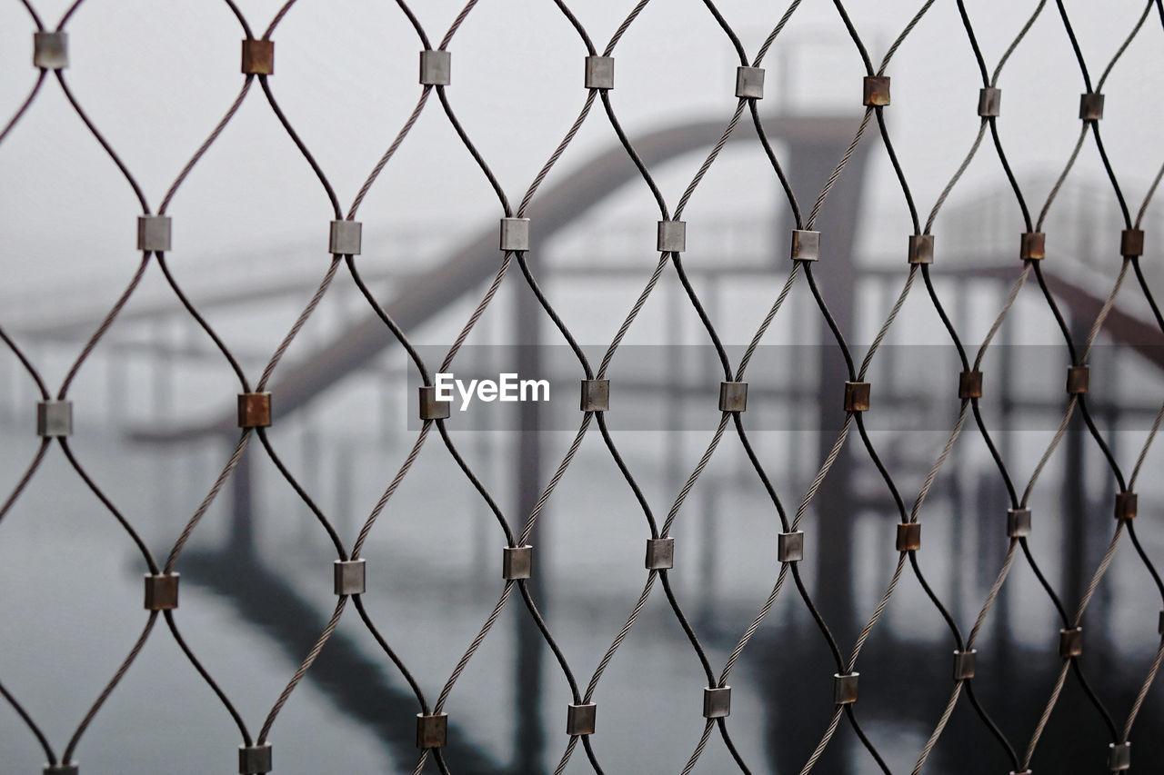 Full frame shot of chainlink fence against bridge