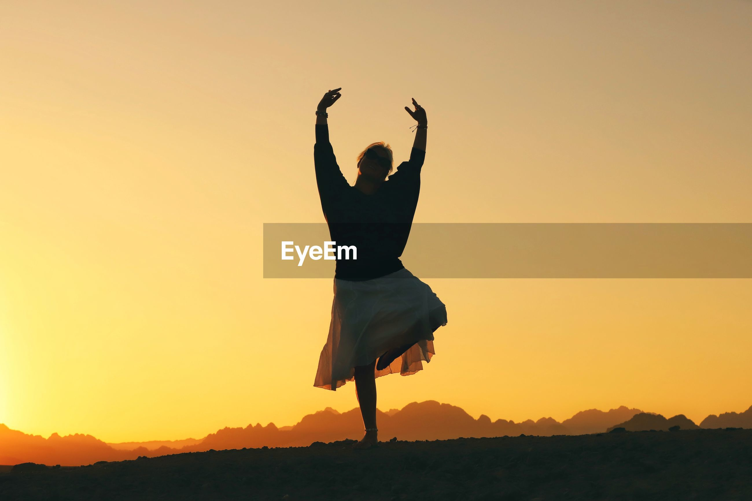 Full length of silhouette woman dancing on land against clear orange sky