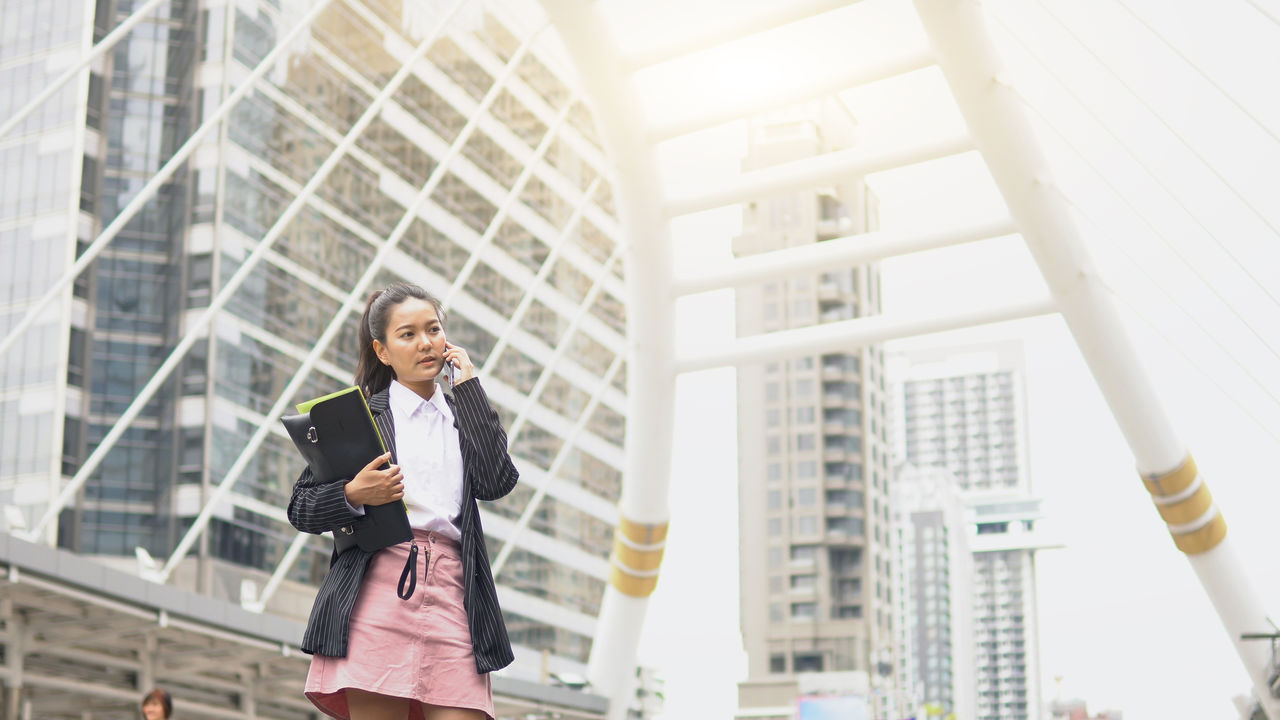 one person, business person, architecture, business, front view, office, well-dressed, women, adult, built structure, real people, businesswoman, three quarter length, day, low angle view, standing, smiling, happiness