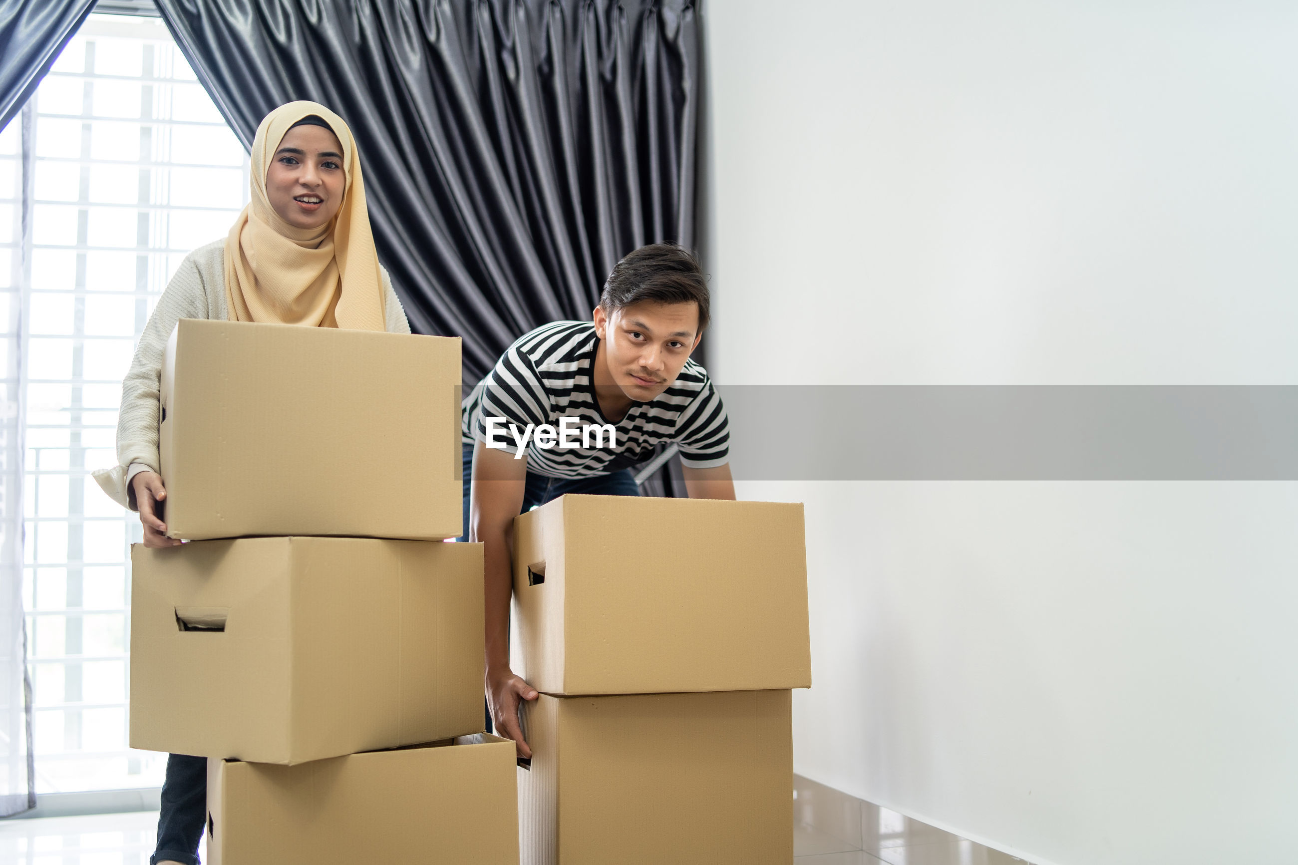 Couple holding cardboard boxes while standing at new home