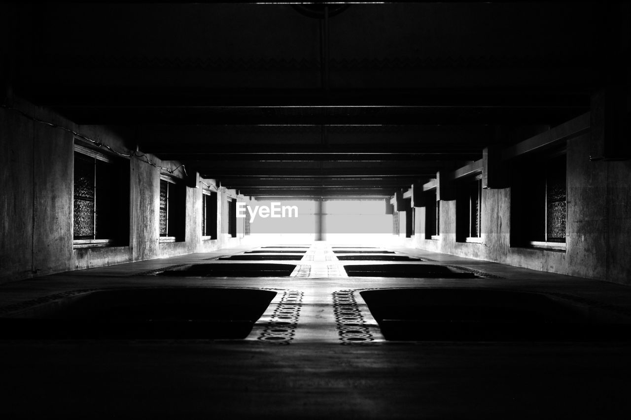 direction, the way forward, architecture, built structure, diminishing perspective, indoors, no people, corridor, illuminated, arcade, empty, building, lighting equipment, flooring, absence, transportation, ceiling, tunnel, in a row, architectural column, dark, long, light at the end of the tunnel, underpass
