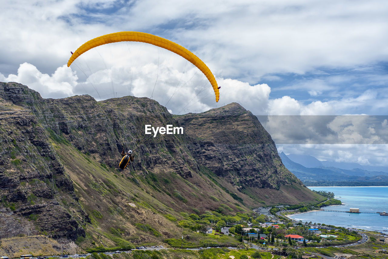 Rear View Of Man Paragliding Against Mountains And Cloudy Sky