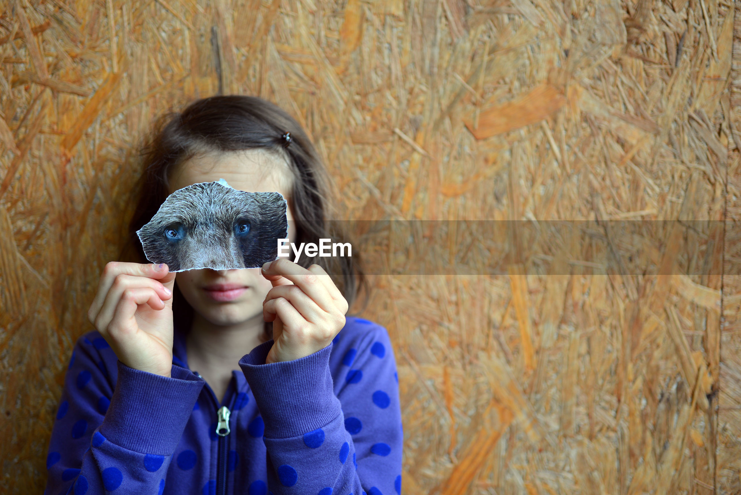 Close-up portrait of girl holding animal eyes against wall