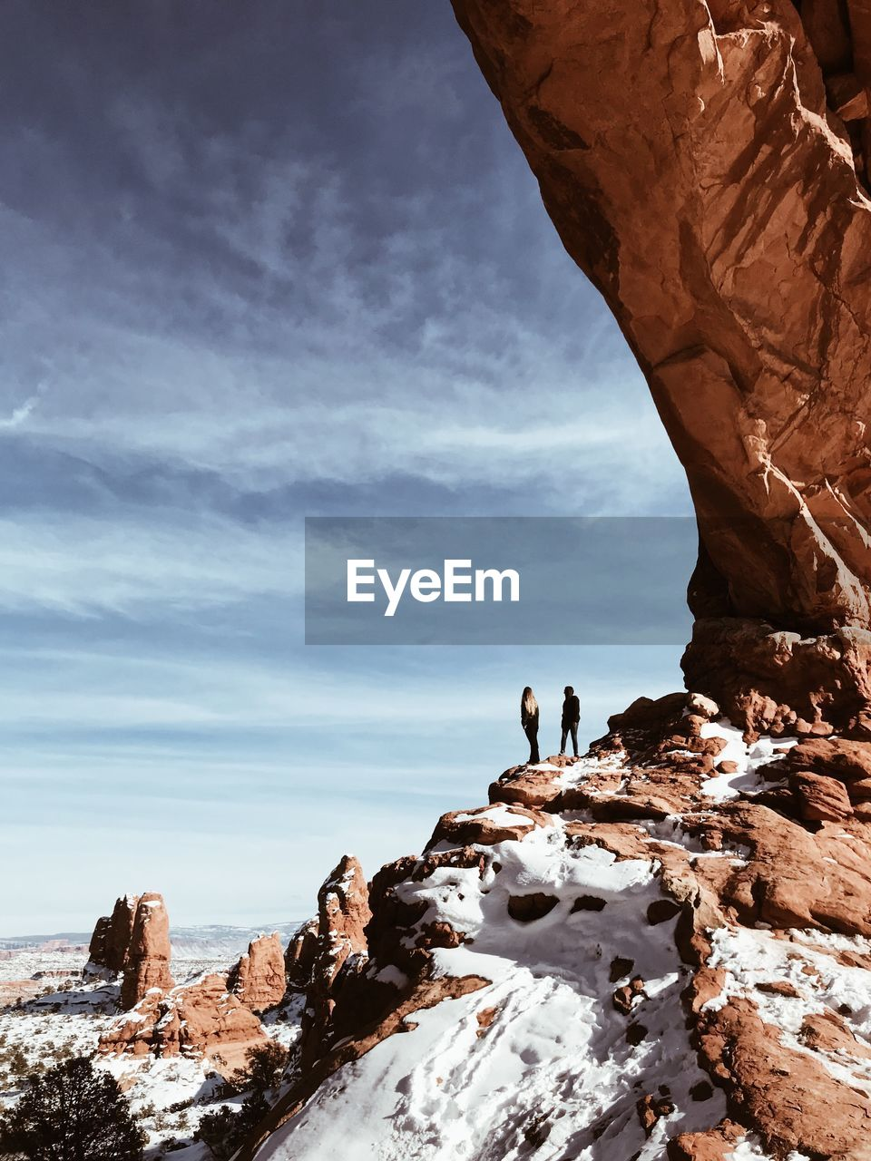 PEOPLE STANDING ON ROCK FORMATIONS AGAINST SKY