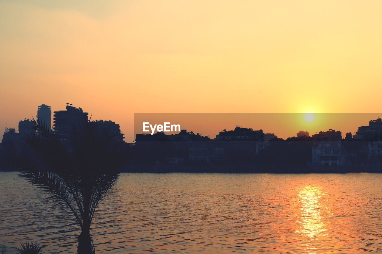 sunset, building exterior, architecture, orange color, built structure, water, nature, beauty in nature, city, no people, outdoors, sun, river, sky, cityscape, scenics, clear sky, tree