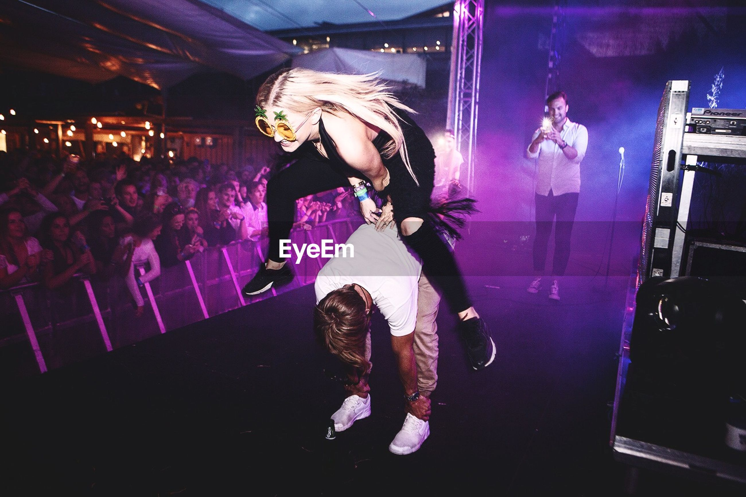 night, illuminated, lifestyles, indoors, arts culture and entertainment, leisure activity, music, performance, enjoyment, men, nightlife, casual clothing, young adult, standing, stage - performance space, holding, full length, event