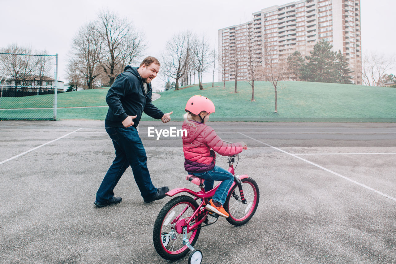 Full length of man encouraging daughter in riding bicycle on walkway