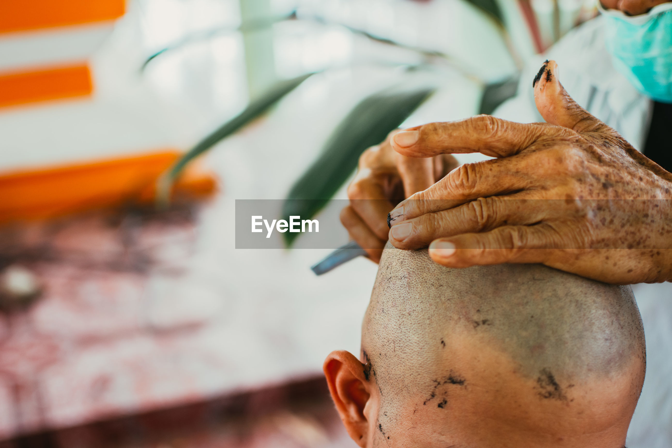 Cropped hand of barber shaving hairs of customer