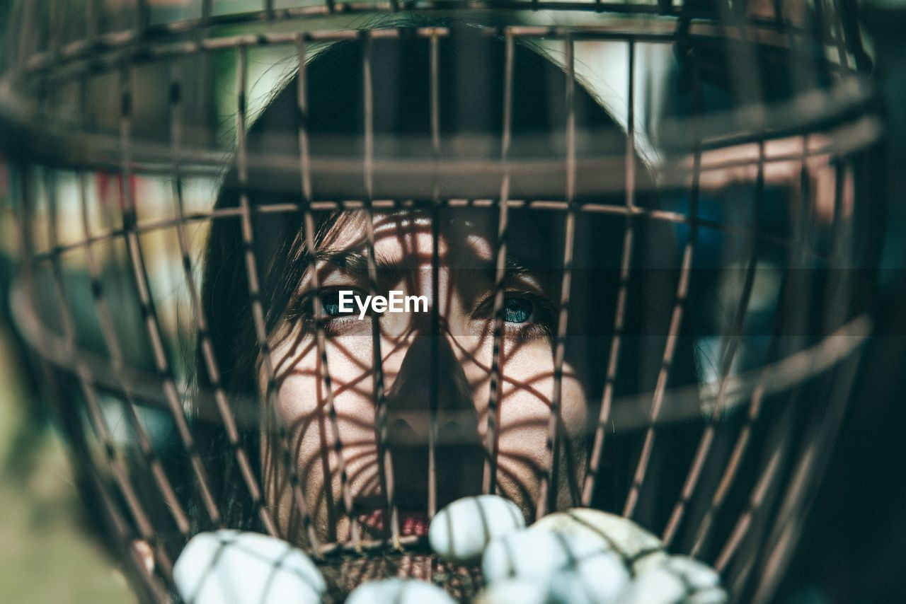 selective focus, close-up, young adult, portrait, one person, metal, cage, day, headshot, real people, focus on foreground, young men, young women, front view, leisure activity, outdoors, barrier, fence, human face