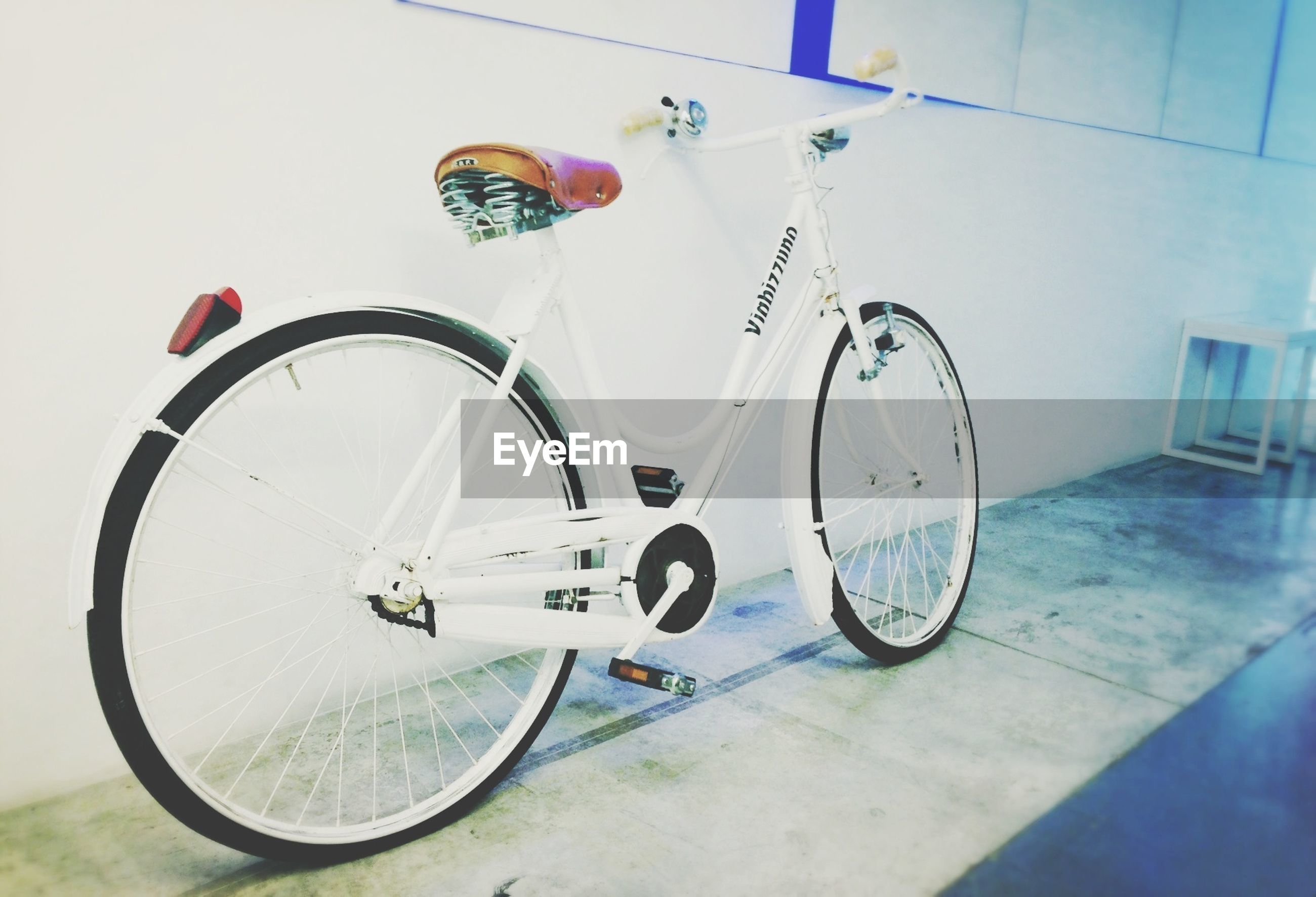 bicycle, transportation, stationary, land vehicle, mode of transport, parked, parking, built structure, wall - building feature, day, architecture, no people, street, sunlight, building exterior, outdoors, blue, hanging, wheel, absence