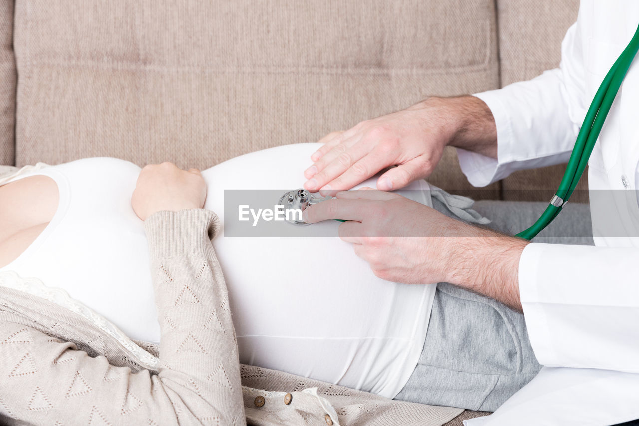 MIDSECTION OF WOMAN WITH HANDS ON TABLE