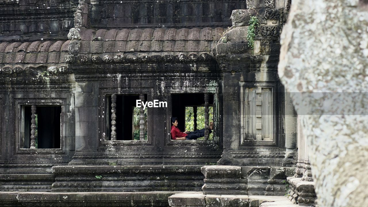 Man sitting in window of old temple