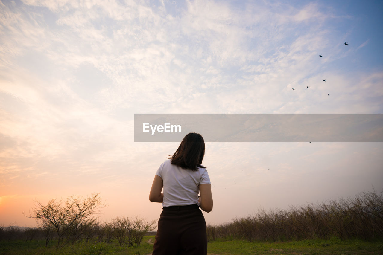 Rear View Of Woman Standing On Field Against Sky During Sunset