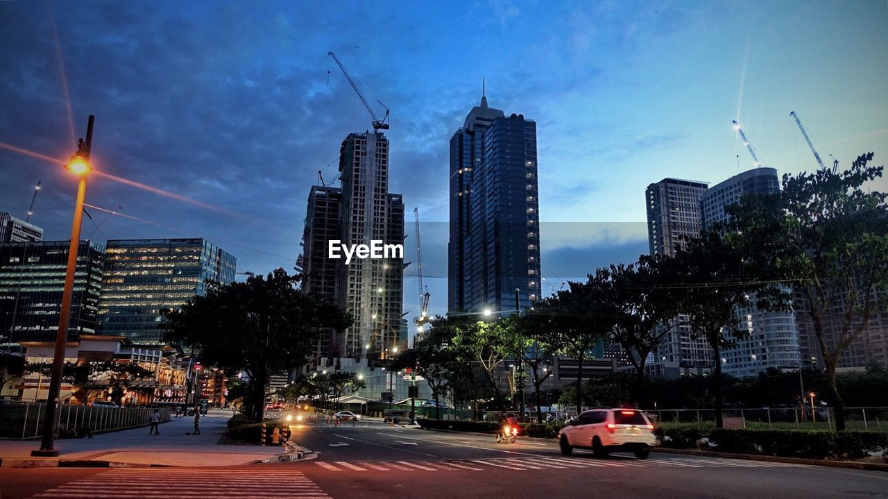 architecture, building exterior, city, built structure, skyscraper, sky, illuminated, car, modern, transportation, no people, outdoors, tree, night, cityscape