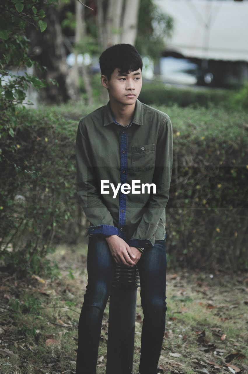 one person, real people, front view, three quarter length, land, young men, lifestyles, leisure activity, casual clothing, plant, tree, day, focus on foreground, young adult, nature, men, looking at camera, standing, outdoors, adolescence, teenager, teenage boys, contemplation