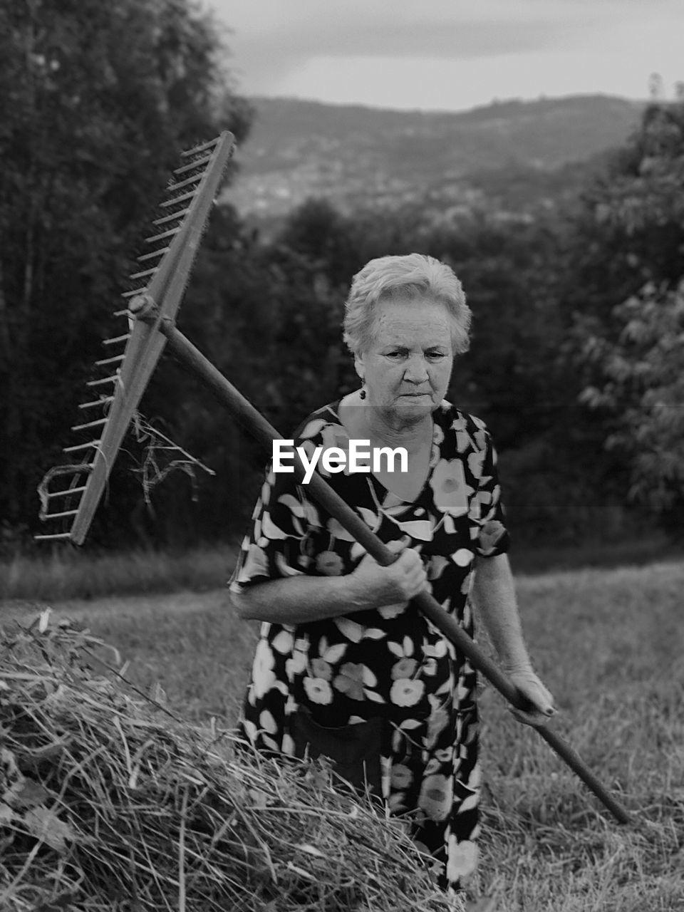 Senior Woman With Rake Walking On Grassy Field