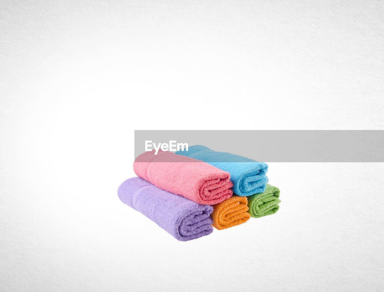 Stack of multi colored towels against white background