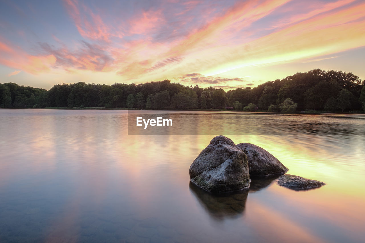 sky, water, sunset, tranquility, beauty in nature, tranquil scene, scenics - nature, cloud - sky, lake, tree, nature, reflection, no people, idyllic, solid, rock, waterfront, orange color, non-urban scene, outdoors