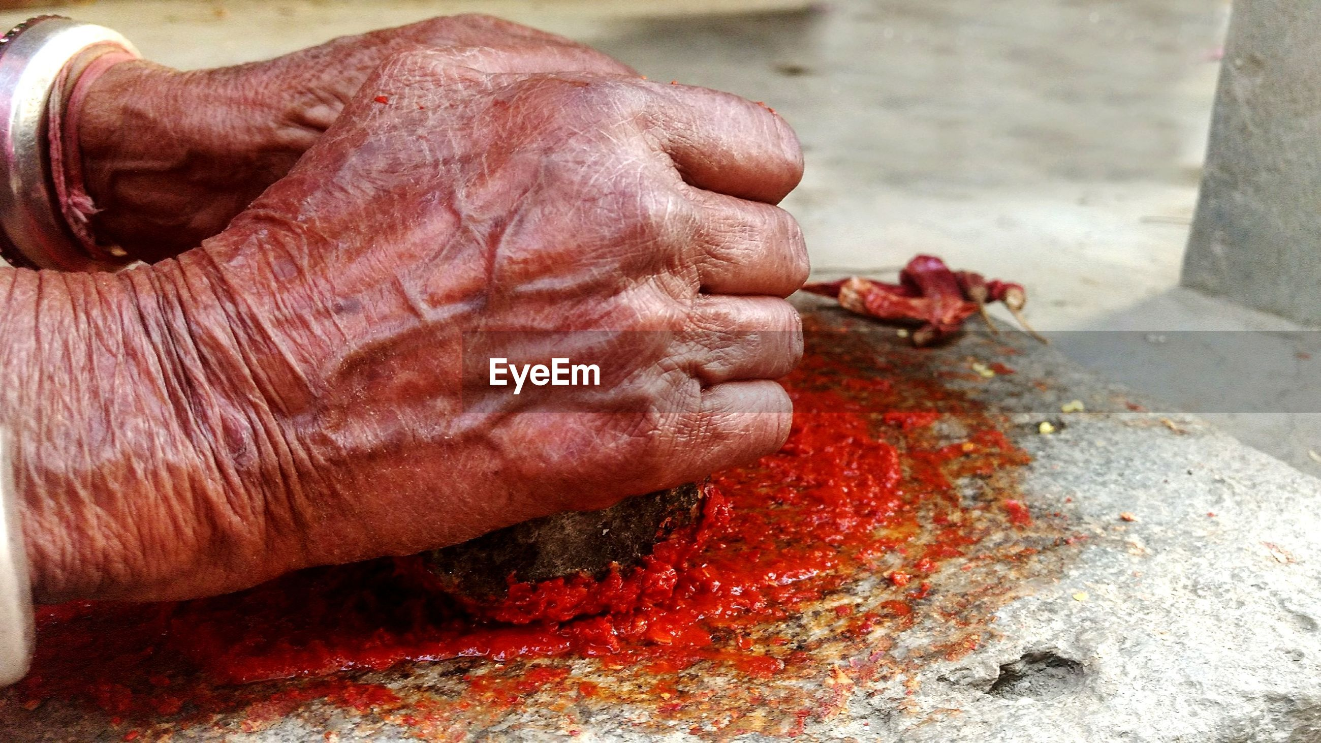 Close-up of hand making chili paste