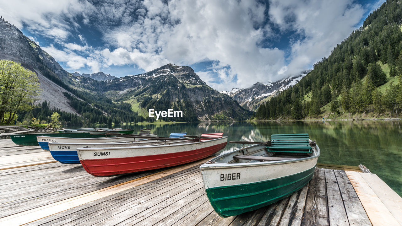 nautical vessel, water, transportation, mode of transportation, mountain, cloud - sky, sky, scenics - nature, beauty in nature, moored, lake, nature, tranquil scene, day, mountain range, tranquility, wood - material, non-urban scene, no people, outdoors, rowboat, snowcapped mountain