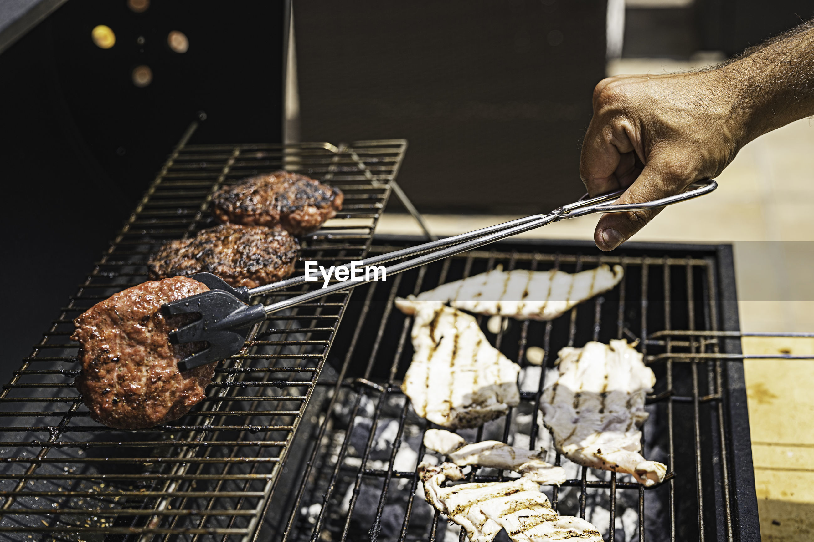 PERSON HOLDING MEAT ON BARBECUE GRILL AT NIGHT