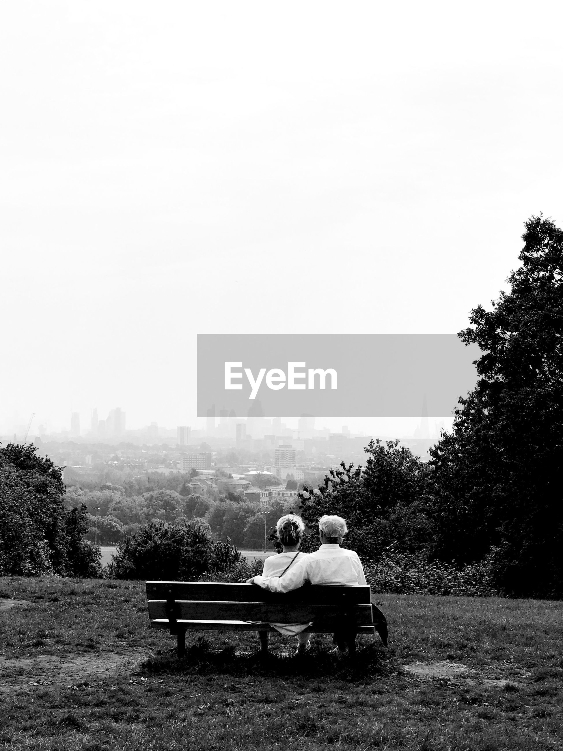 Rear view of senior man and woman sitting on bench against clear sky