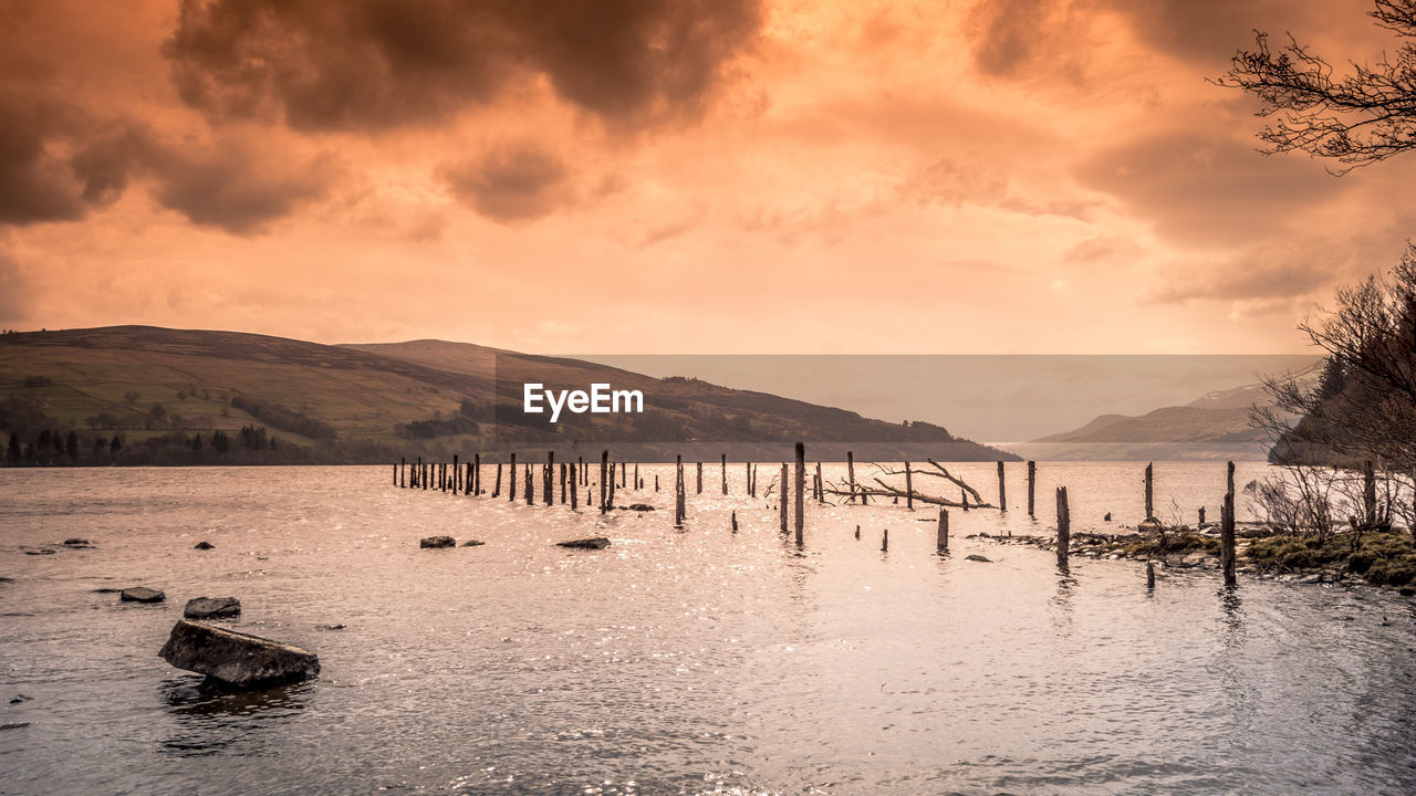 water, sky, cloud - sky, mountain, scenics - nature, beauty in nature, sunset, tranquil scene, nature, tranquility, waterfront, no people, lake, mountain range, wooden post, outdoors, post, non-urban scene