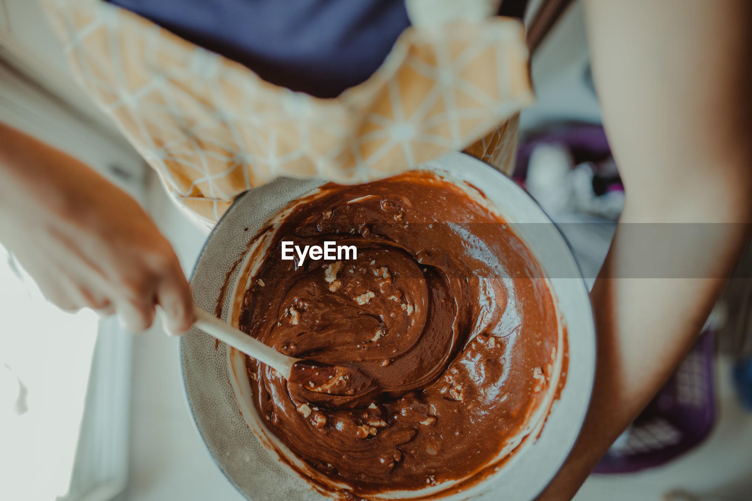 Close-up of woman preparing chocolate cake